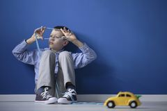 Autistic child playing with string. Autistic child playing with a string and a yellow toy car against a blue wall with copy space Stock Photography
