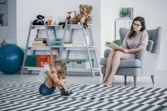 Autistic child sitting on a carpet in a classroom while his counselor is talking to him royalty free stock image