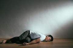 Autistic intellectual disability care concept. Of patient man alone at home disease attack nobody can help lying on wooden floor with white background in dark Royalty Free Stock Images