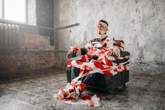 Autistic sitting on a chair in the middle of room Royalty Free Stock Photography