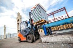 Auto ładowacz z betonowymi blokami zbliża budynek fabrykę Obrazy Royalty Free