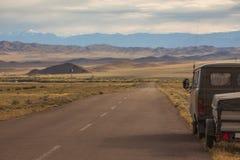 Auto aan de kant van een verlaten weg Stock Foto's