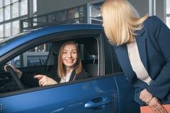 Auto affär, bilförsäljning, consumerism och folkbegrepp - lycklig kvinna med bilåterförsäljaren i auto show eller salong Royaltyfri Foto