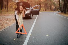 Auto assistance and insurance, troubles while traveling concept. Broken car and auto triangle on road, woman waiting for Royalty Free Stock Image