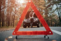 Auto assistance and insurance, troubles while traveling concept. Broken car and auto triangle on road, woman waiting for Stock Image