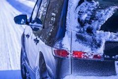 Auto auf der Straße bedeckt mit Schnee und Eis Lizenzfreie Stockbilder