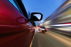 Auto auf der Straße mit Bewegungsunschärfehintergrund in der Nacht Stockbild