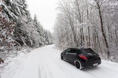 Auto auf einem Schnee bedeckte Straße im Winter Lizenzfreie Stockfotos
