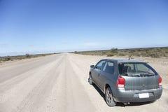 Auto auf einer geöffneten staubigen Straße Lizenzfreies Stockbild