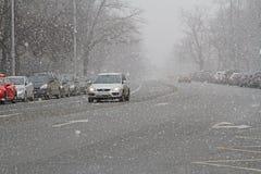 Auto auf einer Schneewinterstraße in den Schneefällen nahe einem Park in Moskau Lizenzfreie Stockbilder