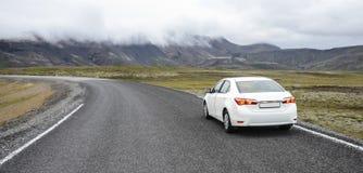 Auto auf einer Straße in einer Landschaft Stockbilder