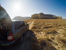 Auto auf einer verlassenen Hochebene vor den Bergen in Kasachstan Lizenzfreies Stockfoto