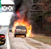 Auto auf Feuer auf der Seite einer Landstraße lizenzfreie stockfotografie
