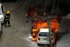 Auto auf Feuer mit Feuerwehrmann Lizenzfreies Stockfoto