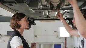 Auto auf mechanischem Aufzug, Mechaniker hilft Kunden, weiblichem Verbraucher stock video footage