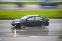 Auto auf nasser Straße an einem regnerischen Tag Stockfoto