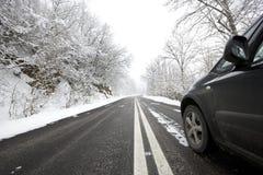Auto auf schneebedeckter Winterstraße Stockbilder