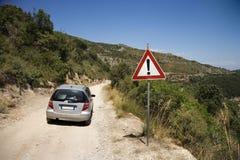 Auto auf Schotterweg mit Achtungzeichen. Stockfotos