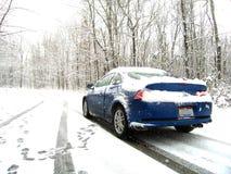 Auto auf Snowy-Straße Stockbilder