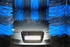 Auto in autowasserette met roterende borstels stock fotografie
