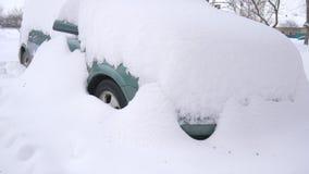 Auto bedeckt durch Schnee, unter schwerem Wintersturm Autos im Yard unter dem Schnee stock footage