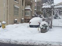 Auto bedeckt im Schnee auf einem Parkplatz einer Wohnung während des wint Stockbilder