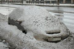 Auto bedeckt mit Schnee in der Straße Lizenzfreie Stockbilder