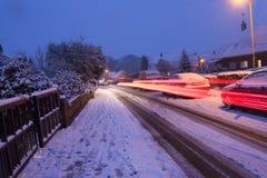 Auto beleuchtet das Strömen vorbei an einem schneebedeckten Abend lizenzfreies stockfoto