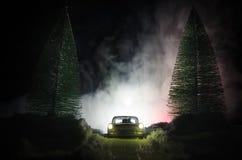 Auto beleuchtet in der Nacht im Kiefernwald mit Schnee Autolichter in der Winterwaldspielzeugdekoration Selektiver Fokus Stockfotos