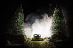 Auto beleuchtet in der Nacht im Kiefernwald mit Schnee Autolichter in der Winterwaldspielzeugdekoration Selektiver Fokus Lizenzfreie Stockfotos