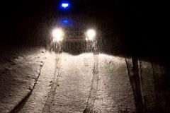 Auto beleuchtet an einem schneebedeckten Abend auf der Straße in einem Blizzard Lizenzfreies Stockbild
