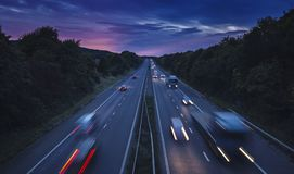 Auto beleuchtet Spuren auf Straße mit getrennten Fahrbahnen an der Dämmerung Lizenzfreies Stockfoto