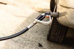 Auto bij benzinestation die met brandstof worden gevuld stock fotografie
