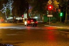 Auto bij verkeerslicht bij nacht wordt tegengehouden die Stock Afbeeldingen