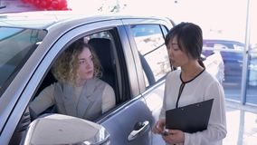 Auto biznes, azjatykciej kobiety samochodowy sprzedawca konsultuje klient dziewczyny w samochodzie i oddaje klucze po pomyślnej s zbiory wideo