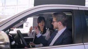 Auto biznes, pomyślnej azjatykciej kobiety samochodowy sprzedawca radzi facet nabywca obsiadanie wśrodku samochodu daje kluczom i zdjęcie wideo