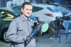 Auto mechanic with buffing machine. Auto body repairs. Mechanic worker portrait with buffing machine for burnish and polishing automobile car body in garage Royalty Free Stock Photography
