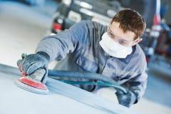 Auto repairman grinding autobody bonnet. Auto body repairs. Repairman mechanic worker grinding automobile car bonnet by grinder in garage workshop. Toned Stock Photography