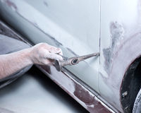 Auto body work. Worker fixing metal part with hummer preparing for filling and painting Stock Images