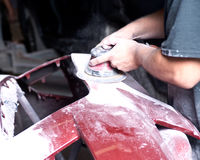 Auto body work. Worker is sanding filler with air sander in auto body shop Royalty Free Stock Photos