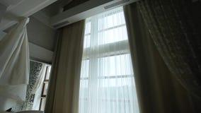 Auto-bokslutet hänger upp gardiner i lägenheten med ett stort fönster arkivfilmer
