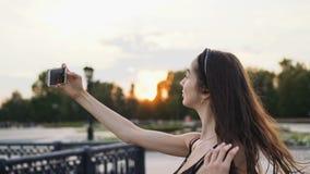 Auto bonito da menina O modelo faz a selfie no telefone um close up do por do sol e exulta-o vídeos de arquivo