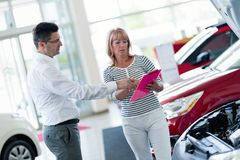 Auto business, car sale, consumerism and people concept. Happy men at auto show or salon Royalty Free Stock Photography