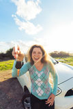 Auto business, car sale, consumerism and people concept - happy woman holding new car key outdoor.  Stock Photo