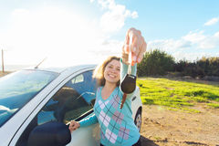 Auto business, car sale, consumerism and people concept - happy woman holding new car key outdoor.  Royalty Free Stock Photo