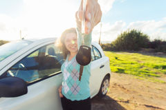 Auto business, car sale, consumerism and people concept - happy woman holding new car key outdoor Stock Image