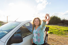 Auto business, car sale, consumerism and people concept - happy woman holding new car key outdoor Stock Photos