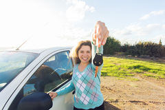 Auto business, car sale, consumerism and people concept - happy woman holding new car key outdoor royalty free stock image