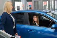 Auto business, car sale, consumerism and people concept - happy woman with car dealer in auto show or salon royalty free stock photography