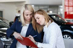 Auto business, car sale, consumerism and people concept - happy woman with car dealer in auto show or salon royalty free stock photos